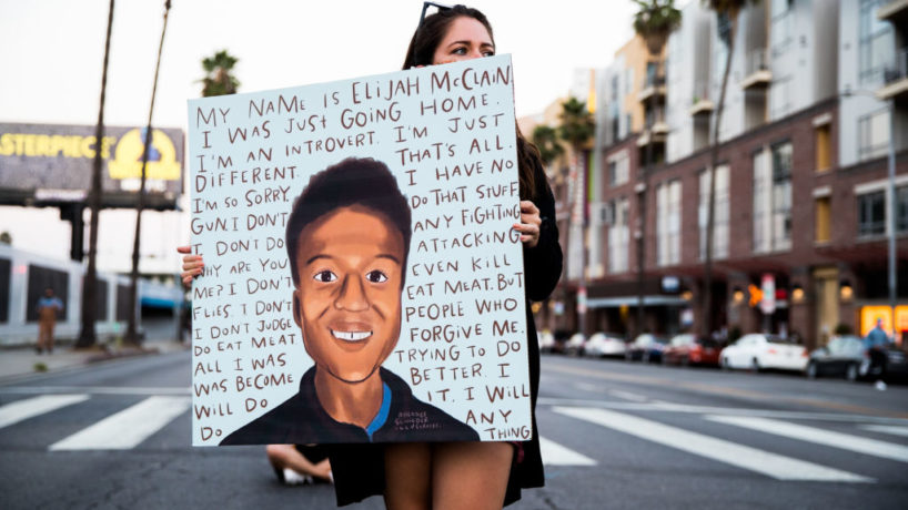 WEST HOLLYWOOD, CALIFORNIA - AUGUST 24: A person holds a sign at a candlelight vigil to demand justice for Elijah McClain on the one year anniversary of his death at The Laugh Factory on August 24, 2020 in West Hollywood, California.