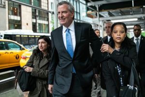 Bill de Blasio, mayor of New York City, center, departs after speaking during a 'Green New Deal' rally in the lobby of Trump Tower in New York, U.S., on Monday, May 13, 2019. De Blasio's Green New Deal aims to ban glass and steel skyscrapers, saying those buildings are much less energy efficient than their brick and concrete counterparts and contribute more to global warming.