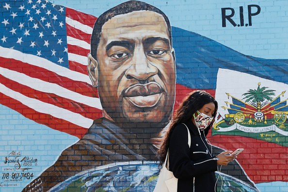 A pedestrian walks past a mural painted by artist Kenny Altidor depicting George Floyd on a sidewall of CTown Supermarket on March 9, 2021 in the Brooklyn borough New York City.