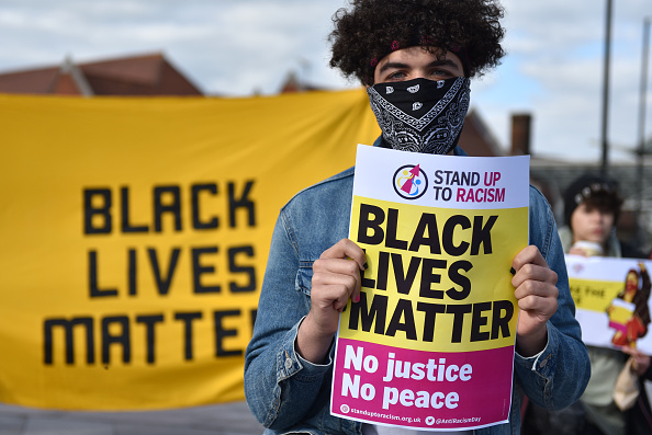 """A person holds up a Black Lives Matter placard as they attend a """"Take The Knee"""" event outside Southend Victoria Station on May 25, 2021 in Southend-on-Sea, England. Stand Up To Racism (SUTR) and the TUC union federation support anti-racists across Britain to take the knee marking the first anniversary of the death of George Floyd. Floyd, an American black man was killed by police in the US state of Minnesota, his death spurred the Black Lives Matter movement in the US, UK and across the globe."""