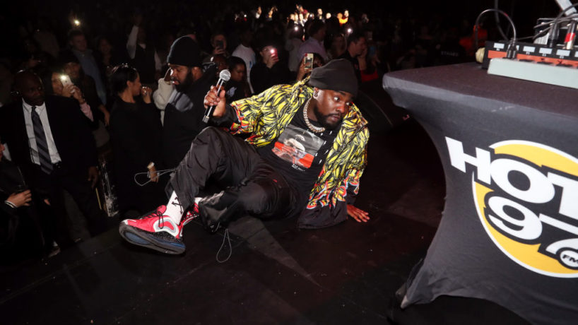 Wale sitting on stage at Hot for the Holidays