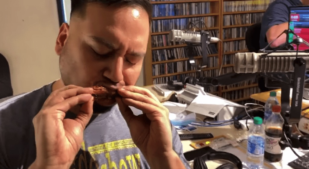 man eating a chicken wing