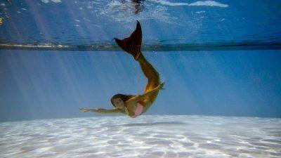 Mermaid swimming under water in a pool