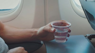 person drinking water on a plane