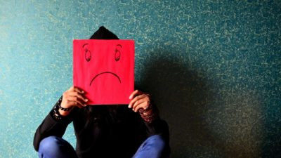 person holding sad face sign