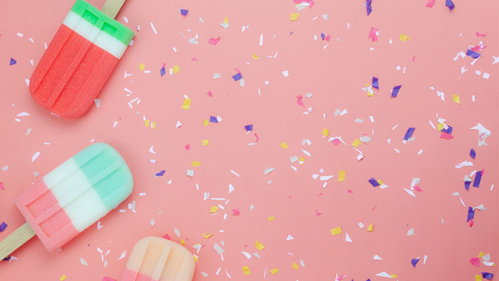 Popsicles on a pink background with confetti