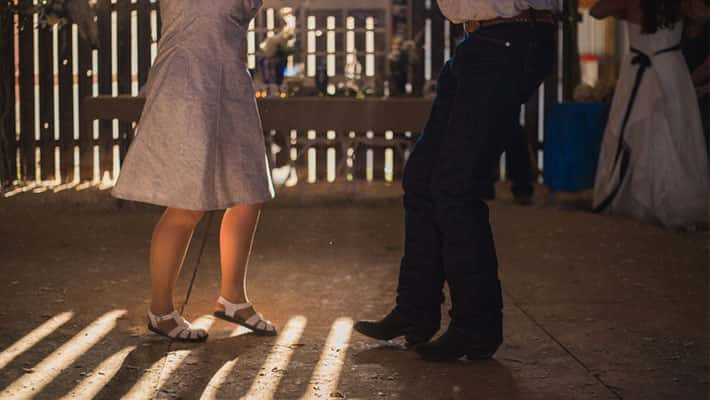 A mother and son share a dance in a barn at a country wedding reception