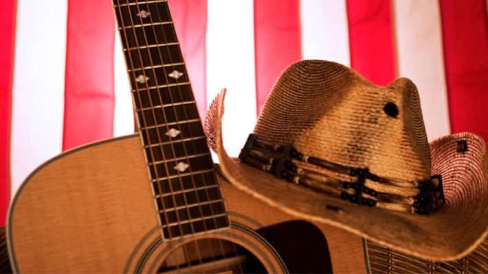 Image of guitar and cowboy hat with American flag in background