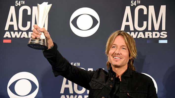 Keith Urban holding up his ACM award for Entertainer of the Year at the 54th ACM Awards