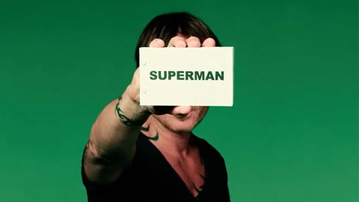 """Keith Urban holding a white sign that says """"Superman"""" in green writing on green background"""