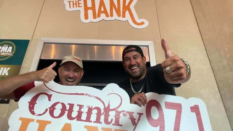 CW and Caleb holding the HANK-FM sign