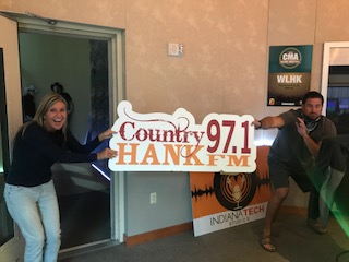 Mindy and Caleb holding HANK-FM sign