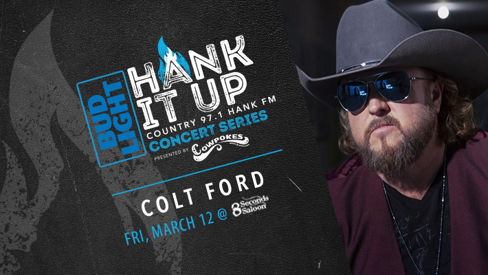 black leather with dark grey flame icon Bud Light HANK IT UP Country 97.1 HANK FM Concert Series Presented By Cowpokes Colt Ford Friday MArch 12th at 8 Seconds Saloon COlt Ford wiht grey cowboy hat and sunglasses on looking towards camera in black v-neck shirt with dark red jacket on top and one silver chain