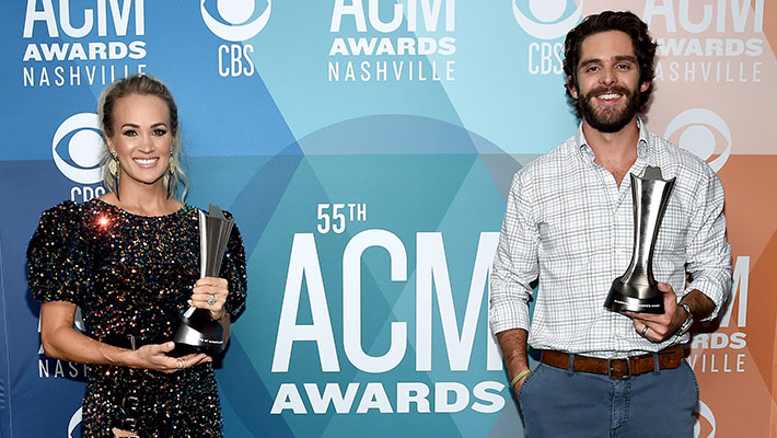 Carrie Underwood and Thomas Rhett holding ACM Awards at the 55th ACM Awards