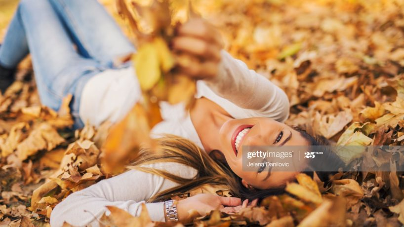 Woman lying in pile of leafs