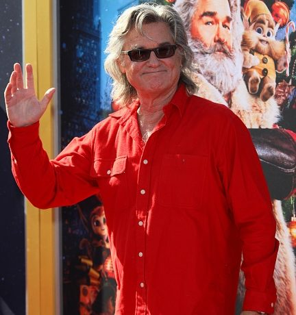 Kurt Russell waves in front of Christmas Chronicles poster