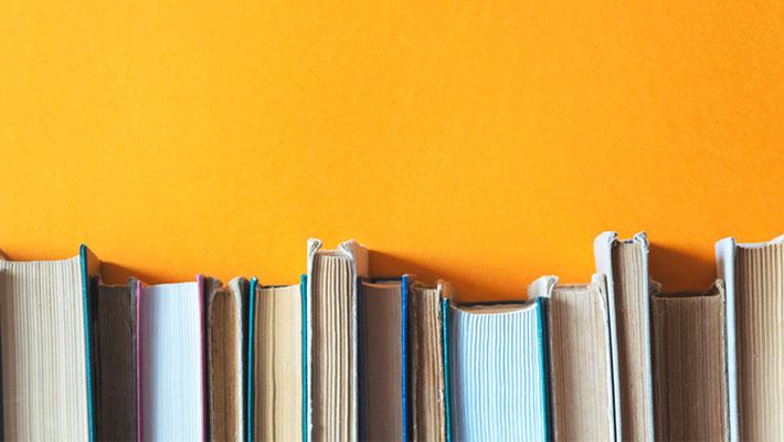 Old books on bookshelves with orange background