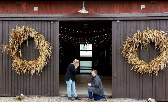 A couple getting engaged in front of a barn