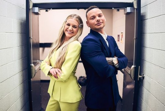 Kane Brown and Kelsea Ballerini standing back to back in the doorway at the CMT Award Show