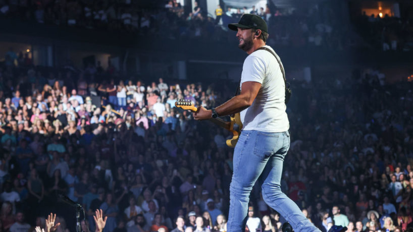 Luke Bryan on stage in white shirt and blue skinny jeans with a baseball hat on singing and playing guitar