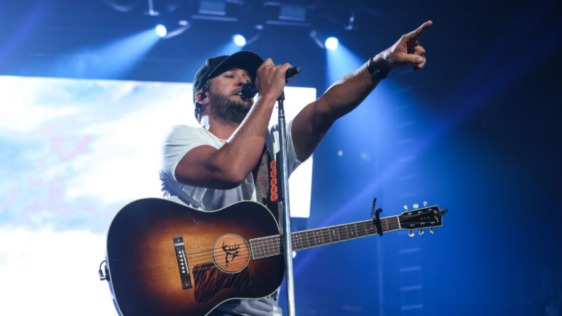 Luke Bryan on stage on his 2021 Proud to be right here tour with a guitar on in a white shirt and skinny jeans singing into his microphone while pointing to the crowd