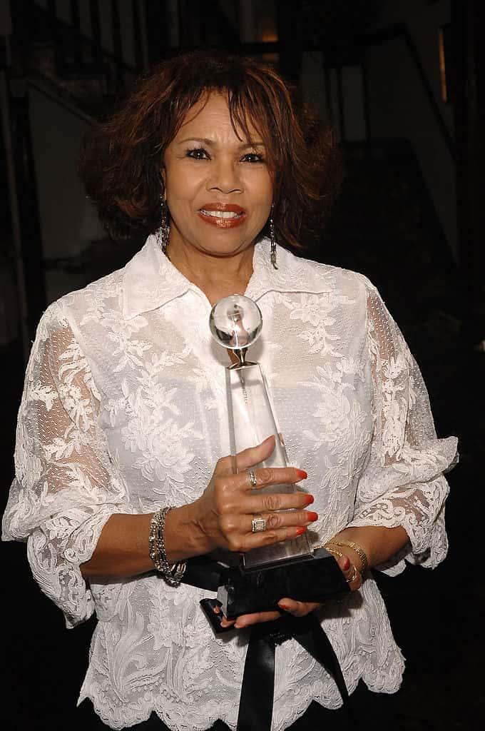 Candi Staton wearing all white while holding an award