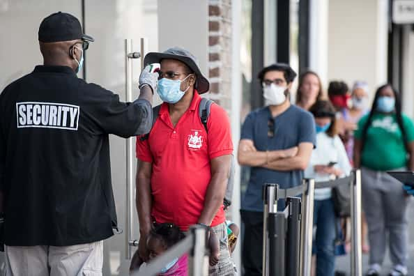 A security guard takes the temperature of a customer outside the Apple Store on May 13, 2020 in Charleston, South Carolina. Customers had their temperatures taken and were required to wear masks at the South Carolina store, as locations in Idaho, Alabama, and Alaska reopened as well following forced closures due to the coronavirus.