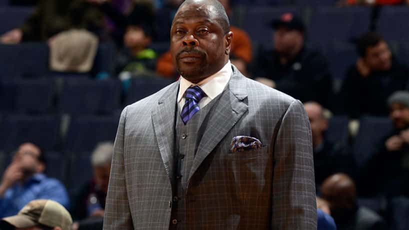Patrick Ewing standing up wearing a suit