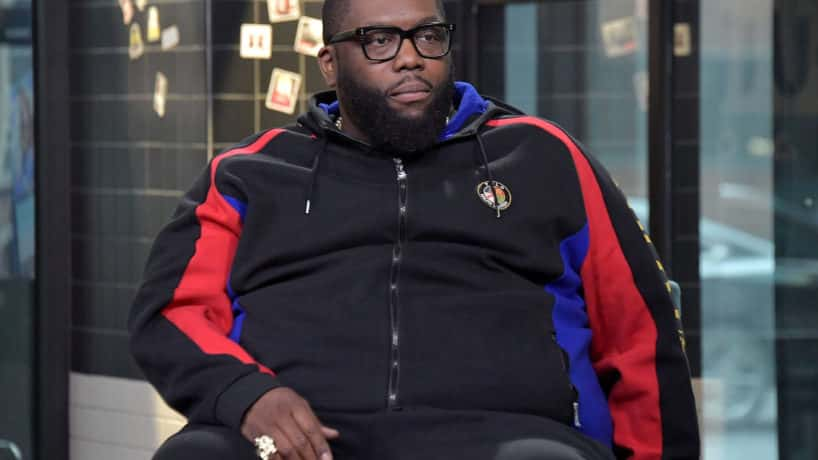 Killer Mike wearing a black sweatsuit, sitting in a chair