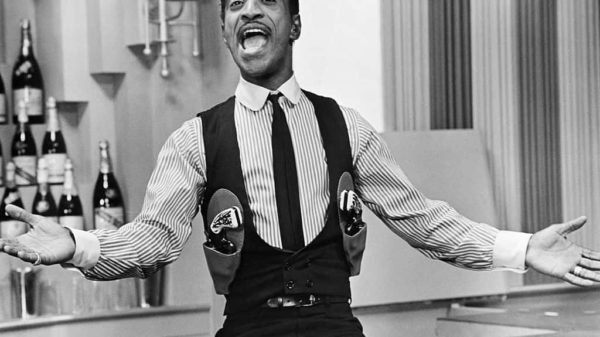 Sammy Davis Jr. with his arms opened and smiling