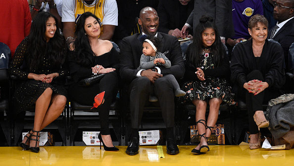 Los Angeles Lakers legend Kobe Bryant seated courtside with his family looks on during a basketball game between the Golden State Warriors and Los Angeles Lakers at Staples Center on December 18, 2017 in Los Angeles, California. The Lakers retired Bryant's #8 and #24 jersey during halftime ceremony. NOTE TO USER: User expressly acknowledges and agrees that, by downloading and or using this photograph, User is consenting to the terms and conditions of the Getty Images License Agreement.
