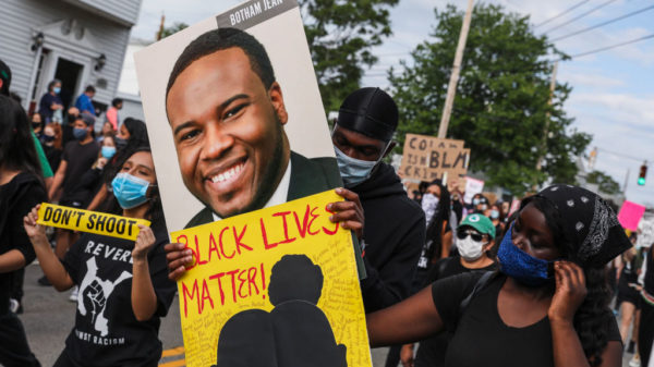 REVERE, MA - JUNE 9: A demonstrator holds a sign for Botham Jean while marching during a demonstration on June 9, 2020 in Revere, MA for George Floyd and other Black Americans killed at the hands of law enforcement. The peaceful march was been planned by Black and Brown Youth, a group based in Revere, who have come together to form Black Lives Matter Revere.