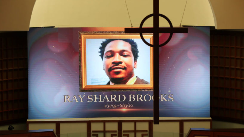ATLANTA, GEORGIA - JUNE 22: A cross hangs from the cathedral ceiling while Rayshard Brooks is memorialized on a screen during his public viewing at Ebenezer Baptist Church June 22, 2020 in Atlanta, Georgia. Brooks, 27, died June 12 after being shot by an officer in a Wendyâs parking lot. Brooksâ death sparked protests in Atlanta and around the country. âEbenezer is a parish for all people, a sanctuary for those who suffer,❠Rev. Raphael G. Warnock, senior pastor of Ebenezer, said in an emailed statement. âRayshard was not a member of our church but he, and his loved ones, are a part of our family. We seek to embrace them, comfort them and walk beside them in the days ahead.❠A private funeral for Brooks will be held Tuesday at the church.