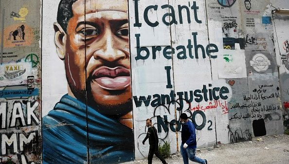 """People walk past a mural showing the face of George Floyd, an unarmed handcuffed black man who died after a white policeman knelt on his neck during an arrest in the US, painted on a section of Israel's controversial separation barrier in the city of Bethlehem in the occupied West Bank on March 31, 2021. - The teenager who took the viral video of George Floyd's death said on March 30, at the trial of the white police officer charged with killing the 46-year-old Black man that she knew at the time """"it wasn't right."""" Darnella Frazier, 18, was among the witnesses who gave emotional testimony on Tuesday at the high-profile trial of former Minneapolis police officer Derek Chauvin. Chauvin, 45, is charged with murder and manslaughter for his role in Floyd's May 25, 2020 death, which was captured on video by Frazier and seen by millions, sparking anti-racism protests around the globe."""