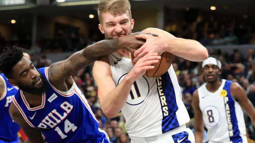 Domantas Sabonis fights for the ball against Norvel Pelle of the Philadelphia 76ers