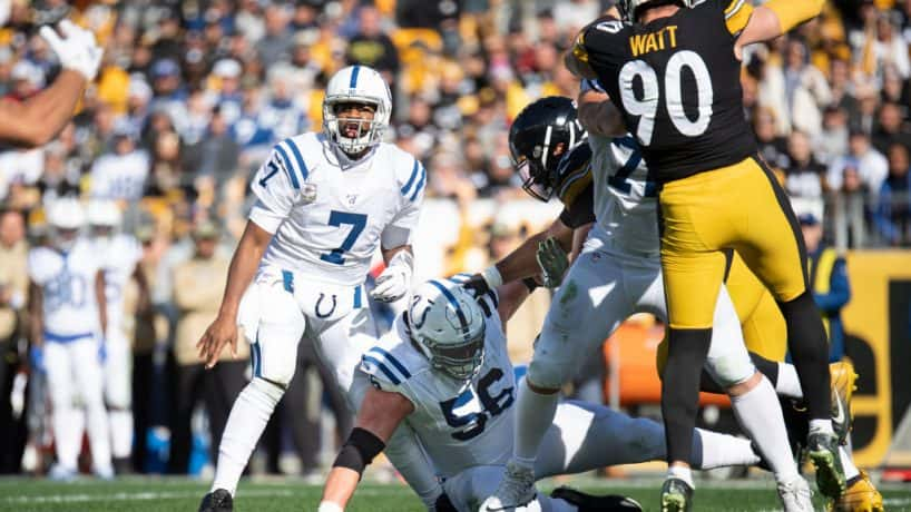 Colts quarterback Jacoby Brissett has his left knee fallen into by teammate Quenton Nelson during a 2019 game.