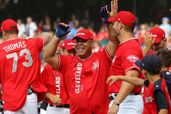 Former MLB All-Star Carlos Baerga celebrates with his teammates after hitting a home run during the Legends & Celebrity Softball