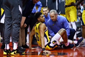 Pacers guard Jeremy Lamb sits on the ground after injuring his left knee during the 2019-20 season.
