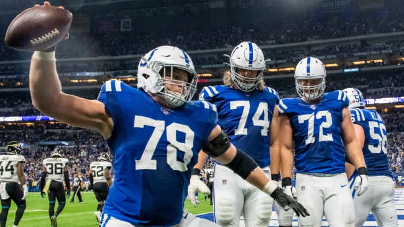 Colts offensive linemen spike the ball during a 2019 game.