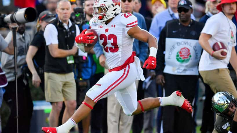 Jonathan Taylor runs down the sideline for Wisconsin in the Rose Bowl