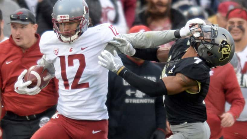 Washington State Dezmon Patmon stiffarms a Colorado player.
