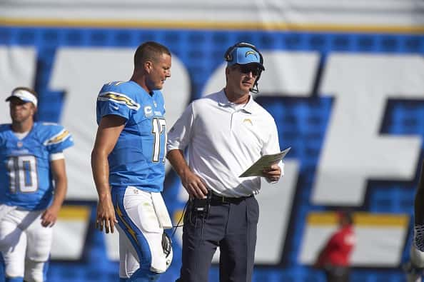 Frank Reich and Philip Rivers talks during a game.