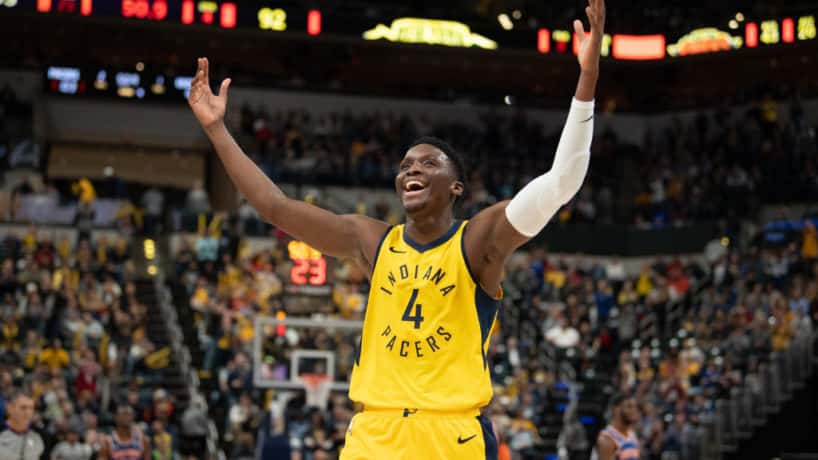 Pacers guard Victor Oladipo raises his hands to the crowd.