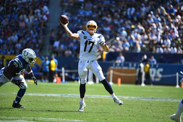 Philip Rivers rolls out of the pocket and throws down the field.