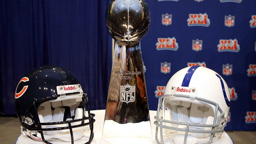 The Vince Lombardi Trophy sits between the Chicago Bears helmet on the left and the Indianapolis Colts helmet on the right on a table in front of an NFL backdrop