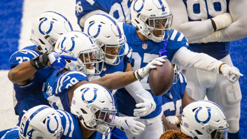 The Indianapolis Colts defense huddles together looking at a camera and celebrates a touchdown in their Week 3 game versus the New York Jets