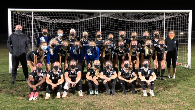The Noblesville Girls Soccer team takes a photo along with their staff with masks on in front of a soccer goal