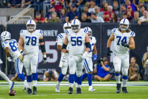 Colts offensive linemen walk up to the line of scrimmage.
