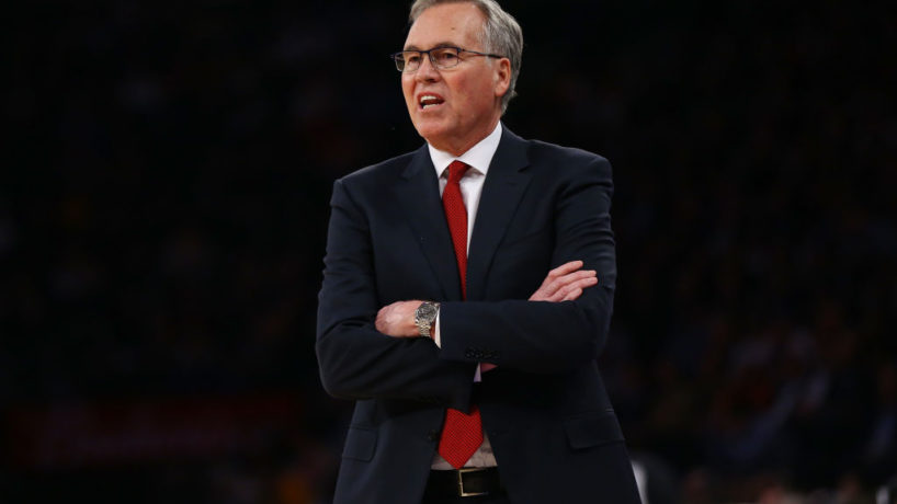 Former Houston Rockets coach Mike D'Antoni looks to the court from the sideline coaching in a game with his arms crossed