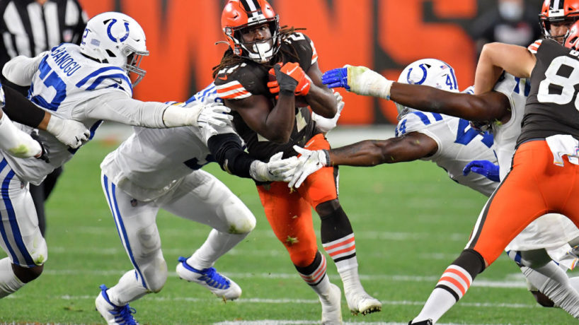 Browns running back Kareem Hunt evades Indianapolis Colts tacklers running through the middle of a few blocks from his teammates
